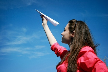 TAKEOFF: Young caucasian girl with paper plane in the hand