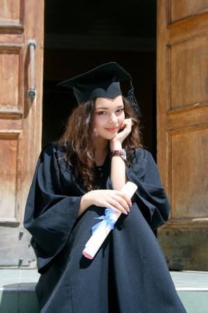 Jonge Kaukasische smiling student in toga dichtbij de universiteit Stockfoto
