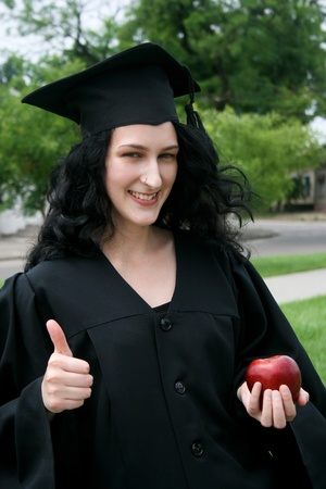 Caucasian student girl in gown with apple photo