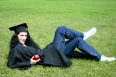 Young caucasian student laying on the grass photo