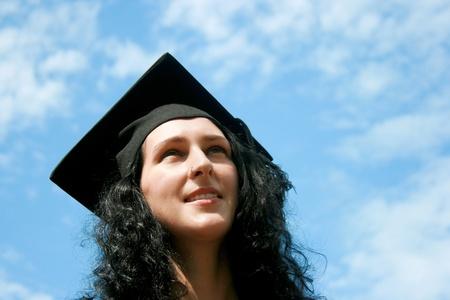 Happy graduate student against blue sky photo