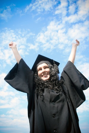Happy graduate student in cloak with open risen arms  photo