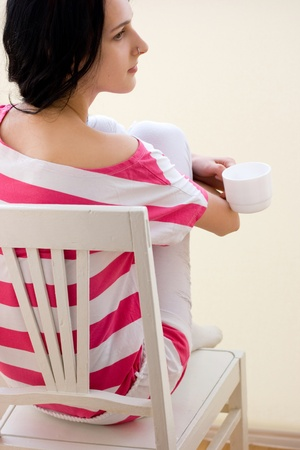Caucasian young woman sitting on the chair and drinking tea photo