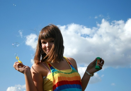 Beautiful girl blowing soap bubbles photo