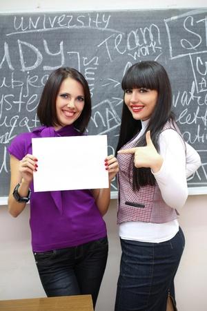 Two young caucasian women near the blackboard Stock Photo - 12812043