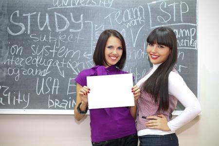 Two young caucasian women near the blackboard photo