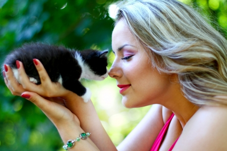 Blonde girl with kitten on her palm Stock Photo