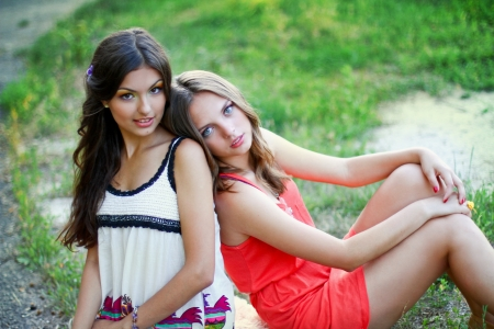 Two young women in dresses sitting near photo