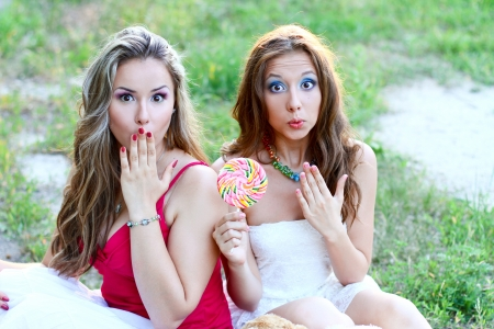 Two surprised friends with lollipop photo