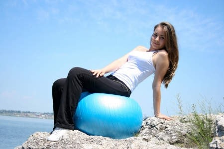 Young woman doing yoga exercises with the ball