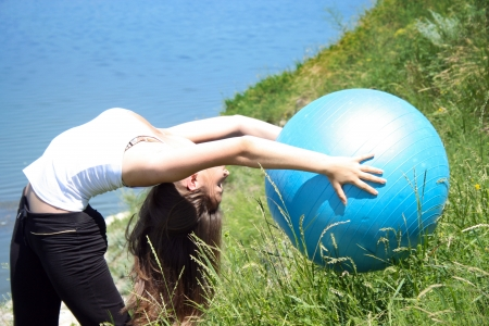 Young woman doing yoga exercises with the ball photo
