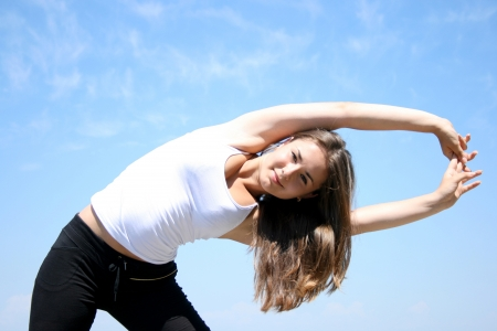 Young woman doing fitness exercises against blue sky Stock Photo