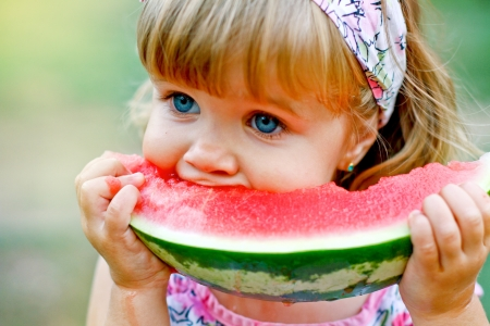 Adorable little girl eats a slice of watermelon outdoors