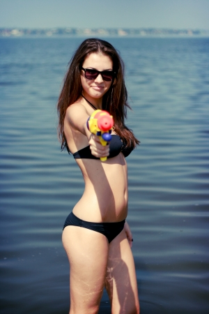 Pretty young women playing water gun at the beach  photo