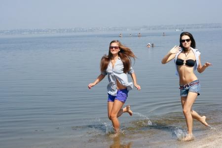 Happy young women running across the beach photo