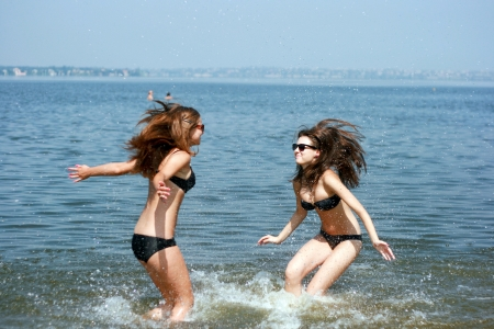 Happy young women playing at the beach  Stock Photo