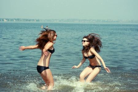 Gelukkige jonge vrouwen spelen op het strand