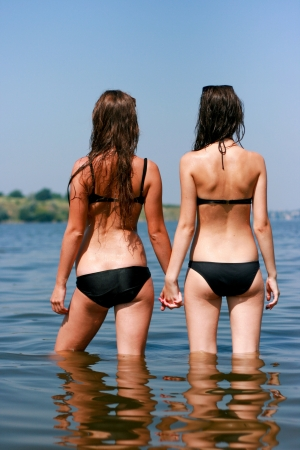 girl ass: Two young women standing in the water from the back