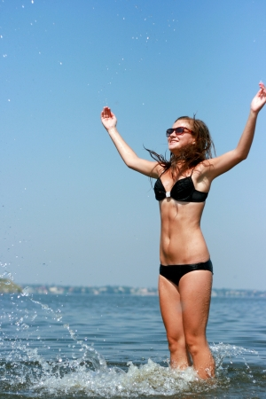 Happy young woman playing at the beach  photo