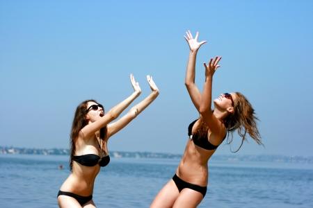Gelukkige jonge vrouwen met een bal spelen op het strand