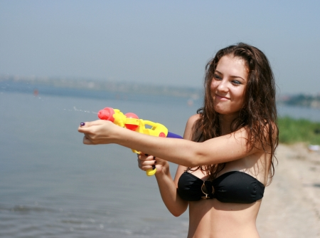 Happy young woman playing with water gun at the beach  photo