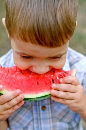 Kaukasische kleine jongen eet een plak van watermeloen buiten