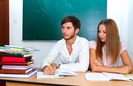 write off: Young caucasian students in the classroom with books at desk girl and boy