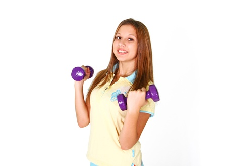 Smiling girl with purple dumbbells in shorts isolated on white background photo