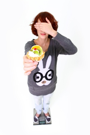 Girl standing on the weigher, holding a cake and shutting her eyes isolated on white background photo