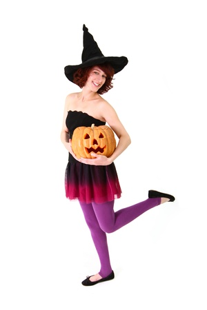 Smiling girl in a witch costume with a pumpkin in her hands photo