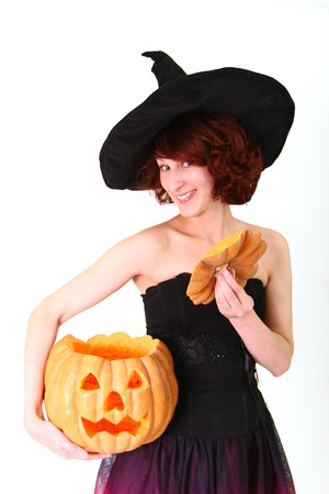 A young woman in a witch costume holding a pumpkin and opening it photo