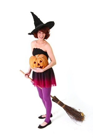 A young woman in a witch costume holding a pumpkin and sitting on a broom photo