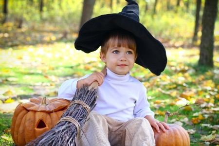 Portrait of a little boy sitting on the ground in the woods with two halloween pumpkins, a broom and a hat photo