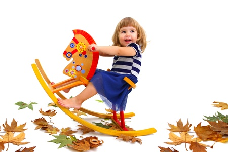 A smiling little girl riding a wooden horse and  on the floor lying yellow leaves