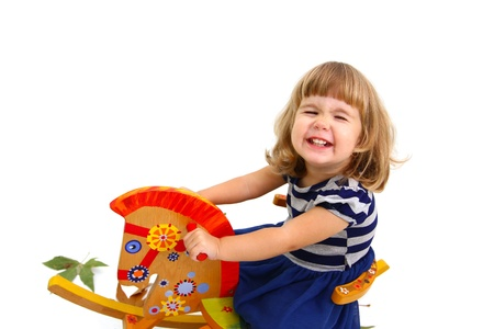 Portrait of smiling little girl who riding on toy horse photo