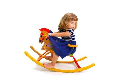 Babe riding on toy wooden horse and looking back photo