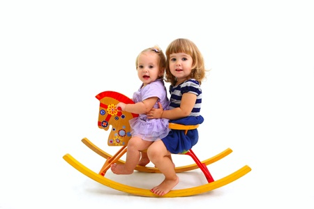 Twee schattige kleine meisjes rijden op een stuk speelgoed houten paard