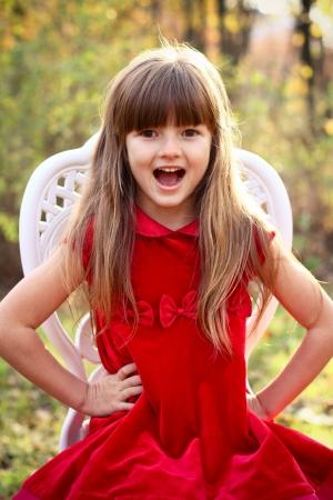 Charmant meisje in een rode jurk zittend op een stoel in de herfst bos Stockfoto