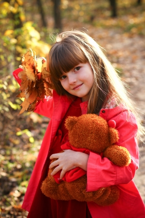 Sweet little girl in the autumn forest holding maple leaves and a teddy bear photo