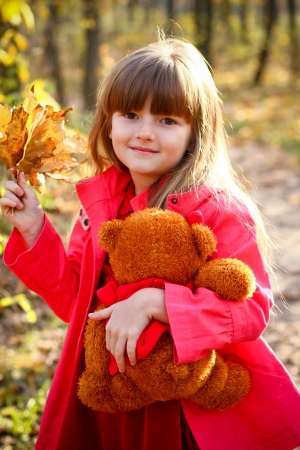 Smiling little girl with maple leaves and teddy bear in hand, in the autumn forest photo