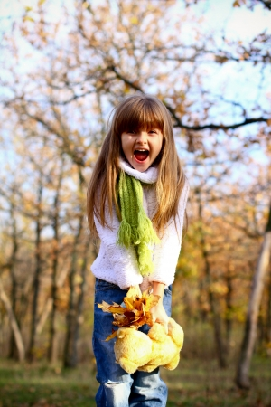 Shouting little girl holding a teddy bear and leaves in autumn forest photo