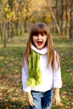 Little girl in the green scarf screaming in the autumn forest photo