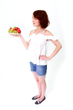 Smiling young woman with grapes, strawberries, apples on a plate isolated on white background Stock Photo - 16300414