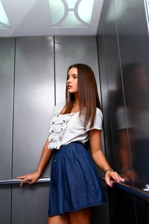 people in elevator: Young business woman in an elevator