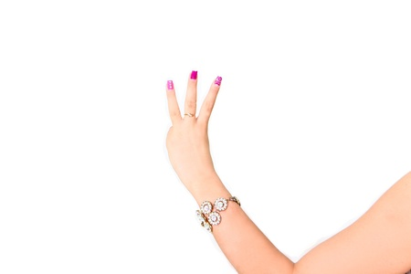 Beautiful woman hand with pink manicure making gesture number three photo