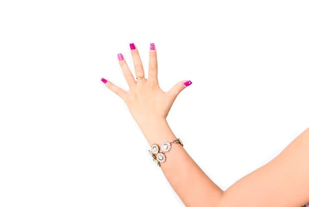Beautiful woman hand with pink manicure making gesture five photo