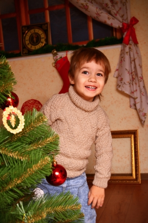 Happy little boy in a beige sweater standing near the Christmas tree photo