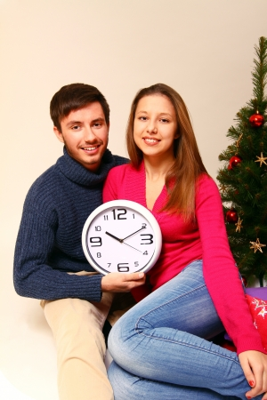 Young man and woman with a clock and a Christmas tree isolated photo