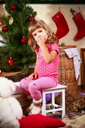 Cute little girl sitting on a white stool near decorated New Year or Christmas tree and eating cookies photo