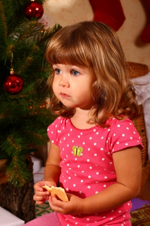 Cute baby sitting near New Year or Christmas tree and eating cookies photo